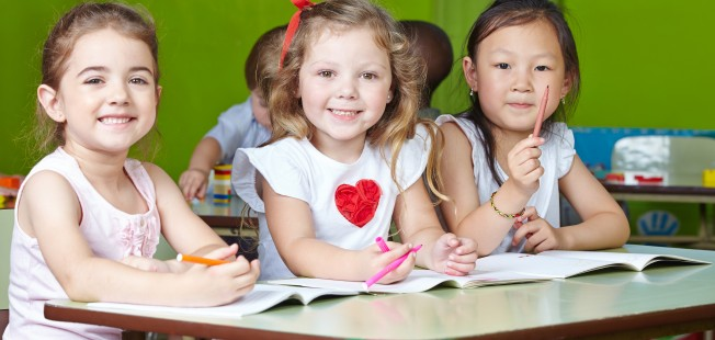 Many Happy Children Drawing In Kindergarten With Pens And Coloring Books